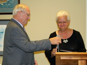 Ruth Hugen, Wayne's Wife, accepts Plaque from President Rob.