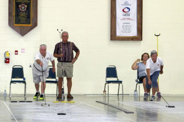 ANDREW PHILIPS/SPECIAL TO THE PACKET & TIMES Coldwater Shuffleboard Club president George O'Reilly, left, makes a shot during an Ontario Shuffleboard Association tournament at the Coldwater Curling Club.