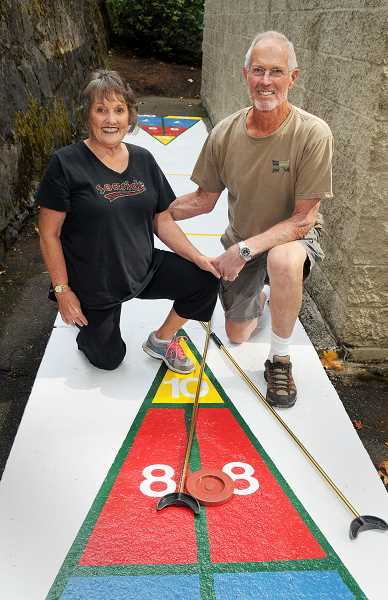 REVIEW PHOTO: VERN UYETAKE - It took a lot of chipping, scraping and painting, but volunteers Dwight and Eloise Willey have finished restoring the shuffleboard court at the Lake Grove Swim Park.