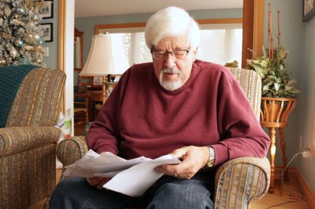 MEHREEN SHAHID/THE PACKET & TIMES Oro-Medonte resident George Maconachie looks over the papers that make up his correspondence with his travel insurance agency he says unjustifiably rejected his claims.